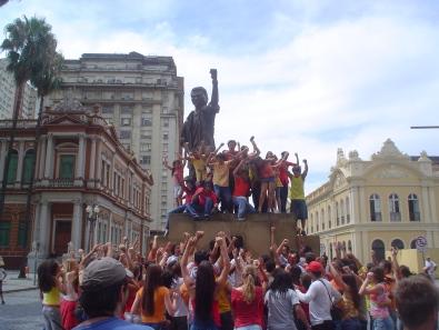 detalhe da filmagem com a escultura e o povo com a Prefeitura Municipal de Porto Alegre e o Mercado Municipal ao fundo
